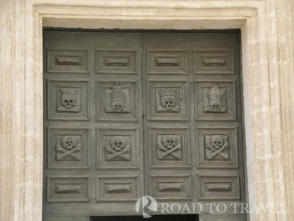 Matera - Cathedral Skull and crossbone carvings on the door of the cathedral.